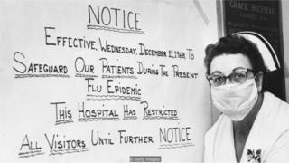 Enfermeira em frente à cartaz da gripe espanhola