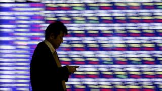 Man walking past share price board