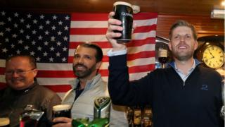 "Donald Trump Jr. (centre), and Eric Trump (right), the sons of US President Donald Trump, behind the bar in Tubridy""s Bar in the village of Doonbeg, Co Clare, on the first day of US President Donald Trump""s visit to the Republic of Ireland"