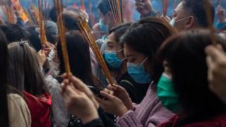 Personas con mascarillas rezando.