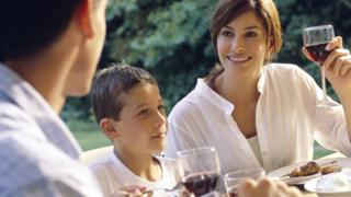 A couple drinking wine, sat with a young boy