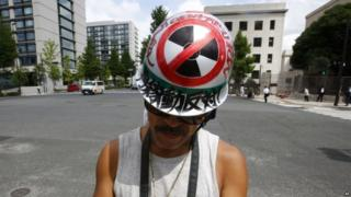 """A protester checks a mobile phone during an anti-nuclear rally in front of Prime Minister Shinzo Abe""""s official residence in Tokyo, Tuesday, 11 Aug 2015"""