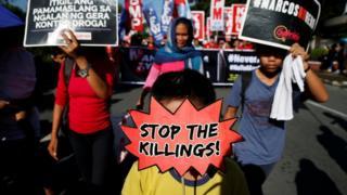 Pessoas exibem cartazes durante um protesto contra o governo em Manila no aniversário da declaração da Lei Marcial de 1972