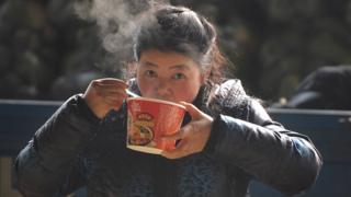 Mulher come macarrão instantâneo