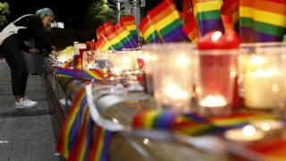SYDNEY, AUSTRALIA - JUNE 13: A woman lights a candle during a candlelight vigil for the victims of the Pulse Nightclub shooting in Orlando, Florida, at Oxford St on June 13, 2016 in Sydney, Australia.