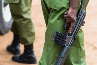 Anonymous uniformed Kenyan police officers hold guns