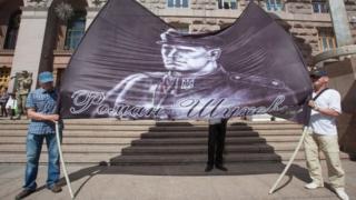 Митингующие под зданием КГГА развернули баннер с изображением Романа Шухевича