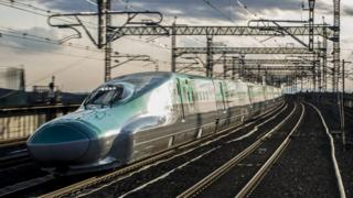 A green bullet train with its long, low nose typical of the type of machine is seen travelling at high speeds against the blurred background of a railway line