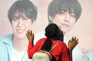 Fan kisses poster of BTS