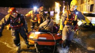 Woman being rescued in lifeboat