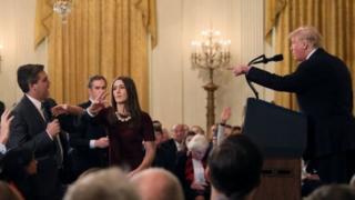 Журналіст Джим Акоста говорить у мікрофон, дівчина хоче забрати мікрофон, Трамп поруч говорить за подіумом