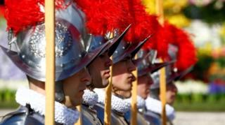 Швейцарские гвардейцы в праздничном облачении стоят в торжественному карауле у базилики Св.Петра в ожидании выхода папы