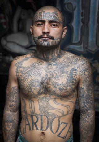Portrait of a heavily tattooed inmate at the Centro Preventivo y de Cumplimiento de Penas Ciudad Barrios taken by Adam Hinton in 2013.
