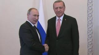 握手するロシアのプーチン大統領(写真左)とトルコのエルドアン大統領