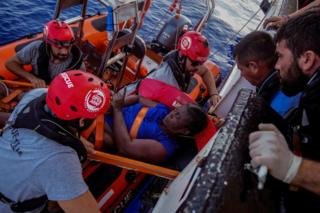 NBA Memphis player Marc Gasol and members of NGO Proactiva Open Arms rescue boat carry Josepha from Cameroon in central Mediterranean Sea