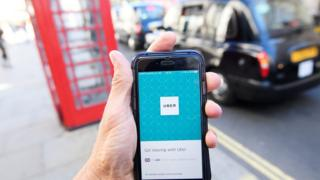 Uber phone app with a phone box and black cab in the background