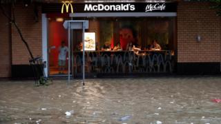 香港杏花邨一家麥當勞餐廳顧客觀看店外被淹沒的馬路(23/8/2017)