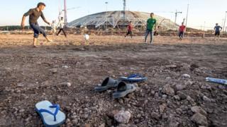 Operários jogam bola perto do estádio em Samara