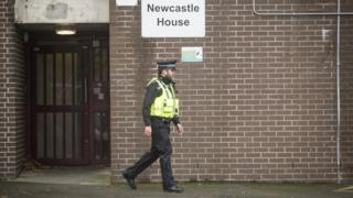 Police officer outside Newcastle House sign