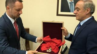 Picture from the Syrian president's Facebook page shows a representative of Syria's foreign affairs giving the Legion d'honneur Grand Croix award to a representative from the Romanian embassy. April 19, 2018