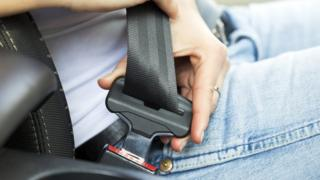 Car passenger fastens seatbelt