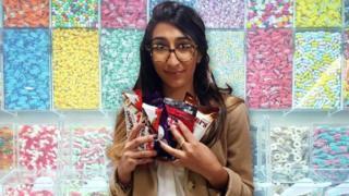 Una mujer con muchos chocolates y dulces en la mano