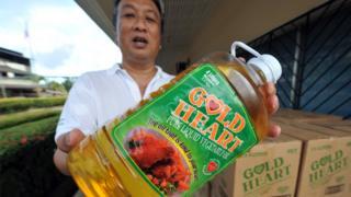Чоловік з пляшкою пальмової олії