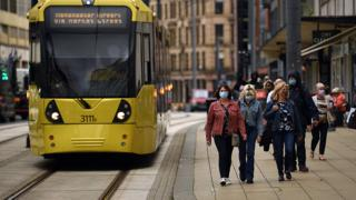 Shoppers wearing masks walk beside a tram route in Manchester city centre