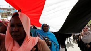 Sudanese protesters march under an national flag outside the defense ministry compound in Khartoum, Sudan, on 29 April 2019.