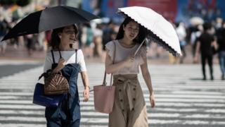 Women shield themselves from the sun with umbrellas in Tokyo on July 24, 2018