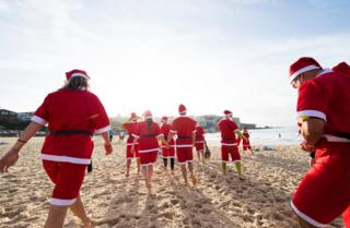 A pack of 320 surfing Santas embrace the Christmas spirit in Australia, breaking the Guinness World Record for the largest surf lesson.