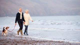 Two pensioners walking along beach
