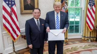 Donald Trump and North Korea's Kim Yong Chol stand with the letter