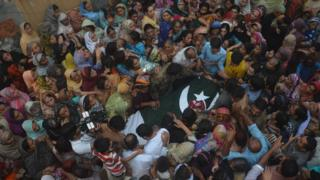 People surround the dead body of a Pakistani soldier allegedly killed by Indian firing, during a funeral in Faisalabad, Pakistan, Thursday, Sept. 29, 2016