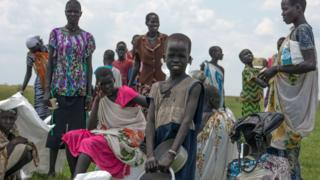 Internally displaced women and children waiting for their food ration after an humanitarian airdrop by the World Food Programme