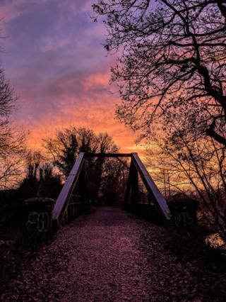A multi-coloured sunset over a bridge