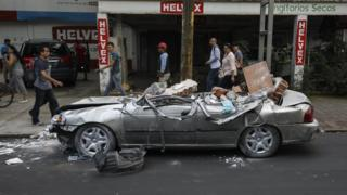 A car crushed under large chunks of rubble