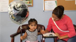 Mujer hispana y su niña con un globo en el Hispanic Outreach Center, condado de Pinellas