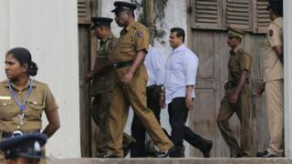 Sri Lankan police and prison officers escort former lawmaker Duminda Silva after he was sentenced to death, at a court complex in Colombo, Sri Lanka, Thursday, Sept. 8, 2016.