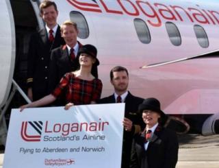 People pose on Loganair plane steps