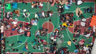 Migrants sleep on a basketball court