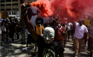 A man holds a smoke grenade as thousands of people march in Denver, Colorado, 30 May 2020