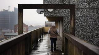 Woman walks away from camera along elevated walkway on housing estate