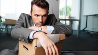 موظف يحمل متعلقاته استعدادا لترك وظيفته