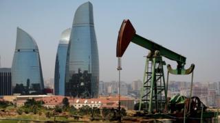 Нефтяная вышка на фоне небоскребов в Азербайджане