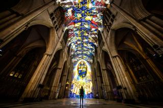 A woman looks at a light projection in a cathedral
