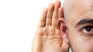 """Homem coloca mão perto do ouvido em gesto que indica uma busca por """"ouvir melhor"""""""