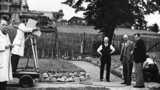 Picture shows gardening in the grounds of Alexandra palace featuring C.H. Middleton (centre) discussing the relative merits of various paving stines with the contractor Mr Moss (left).