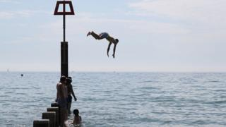 A man jumps off a groyne into the sea as they enjoy the hot weather at Bournemouth beach in Dorset
