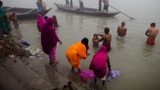 people wash themselves as they take their morning bath in the Ganges river during the Sonepur Mela on November 15, 2011